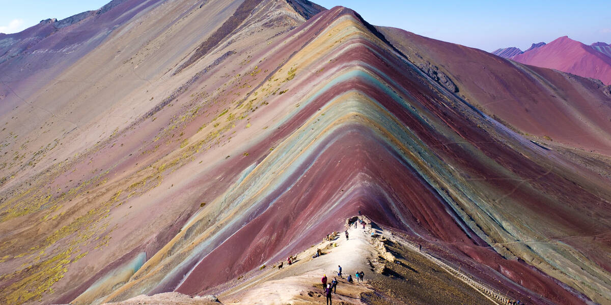 Backpackers at the top of Rainbow Mountain in Cusco, Peru