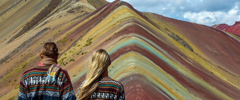 Backpacker couple wearing alpaca sweaters at Vinicunca Rainbow Mountain in Cusco, Peru