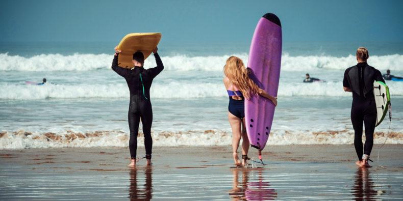 Des surfeurs qui entre à l'eau sur le spot de surf de Mancora.