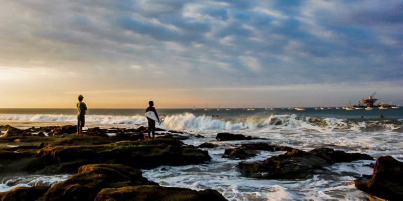 Un surfeur debout sur la plage face à la vague de Cabo Blanco dans le nord du Pérou.