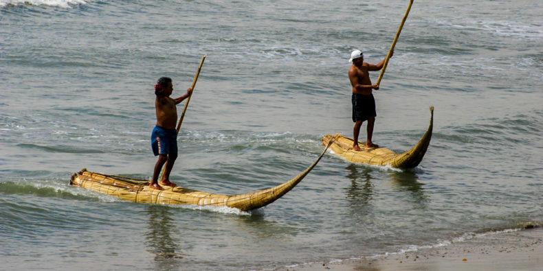 Des pêcheurs debouts sur leur canoë en roseau de totora à Huanchaco dans le nord du Pérou.