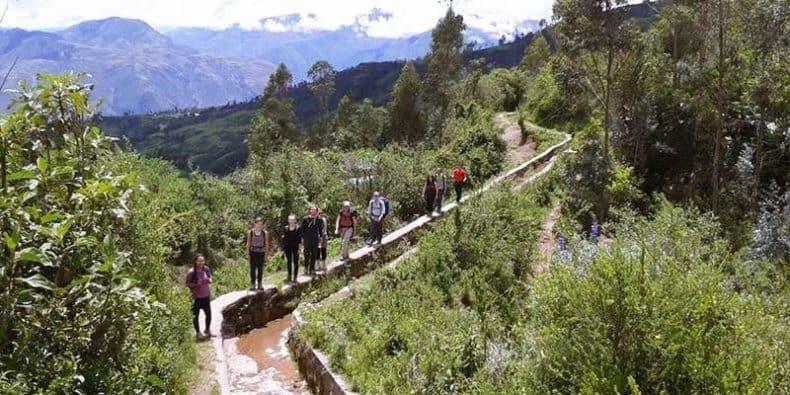 Salkantay trekkers walking along a section of an Inca aqueduct