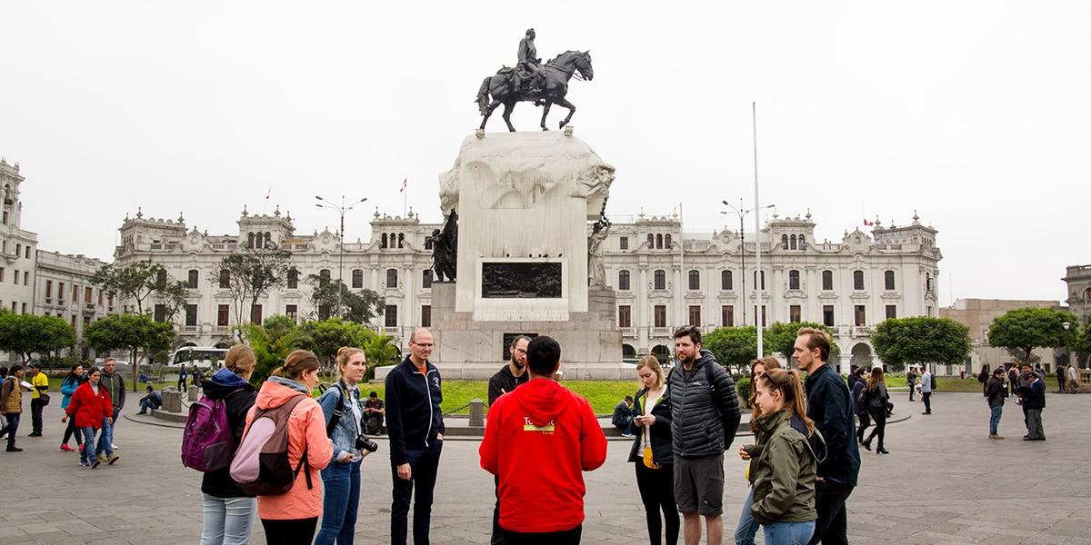 grupo de turistas en el centro de lima escuchando a su guía - tours en Lima