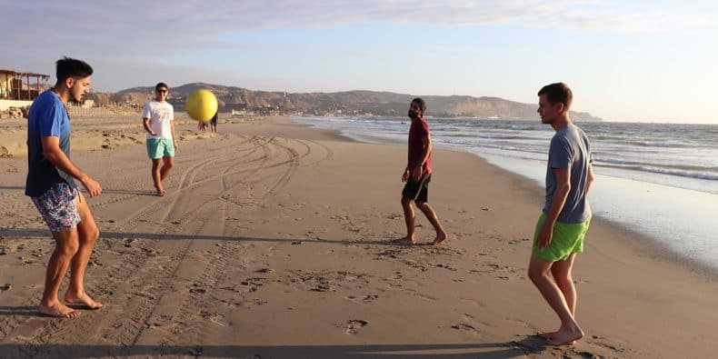 amigos jogando futebol na praia de máncora